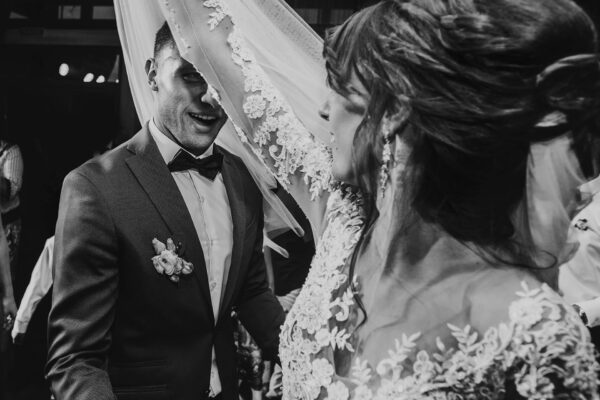 happy bride and stylish groom dancing at wedding reception. gorgeous wedding couple having fun and partying in restaurant. newlywed emotional moment. space for text. black white